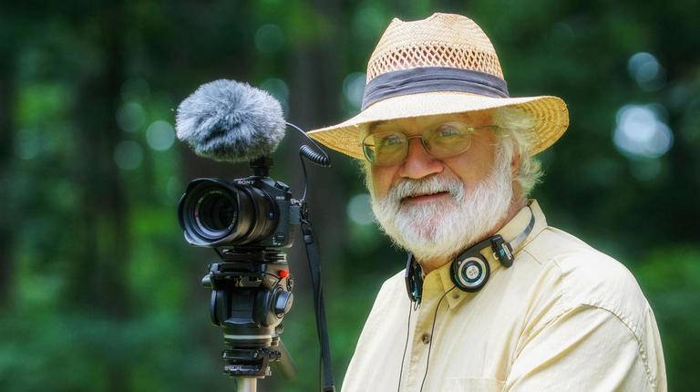Picture of nature photographer Bob Krist, wearing a straw hat and yellow shirt, standing with his camera in front of a forest during daytime.