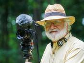 National Geographic Photographer Bob Krist standing with his camera in front of a forest